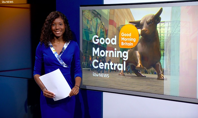 Graduate Monifa Bobb-Simon standing in front of a Good Morning Central TV screen with script in her hand.