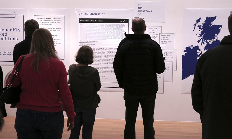Group of people looking at exhibition posters