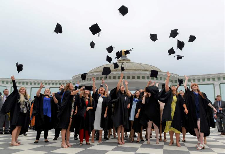 Students throwing mortarboards in air
