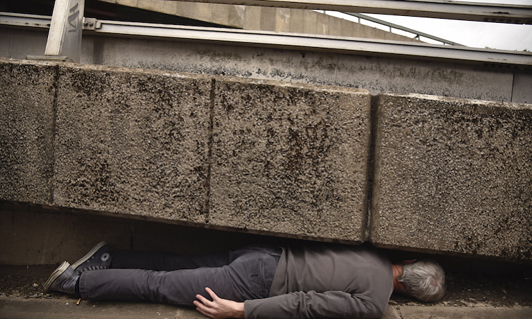 man lying under concrete highway