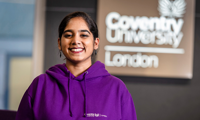 Student ambassador in purple hoody standing in front of 'Coventry University London' sign
