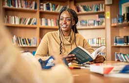 Female wearing a beige top is reading in a library