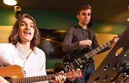 Two guys playing guitars in a music studio