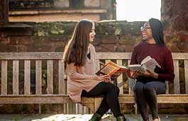 Two females sitting on a bench in front of an old building holding books