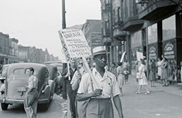 three men with picket boards walking down a street protesting with passers by in the background