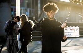 Media Production student with a clapperboard and two students in the background with filming equipment