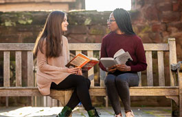 Two students sitting in the Coventry Cathedral ruins