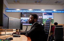 Student sat at desk looking at computer monitors.