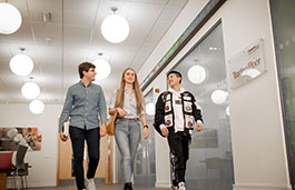 3 students walking in a corridor in Business Law buildling