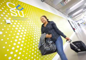 female rolling a suitcase alongside a wall with CUSU logo on it