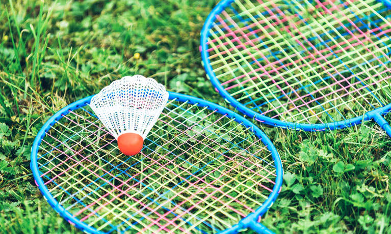 Two badminton rackets and a shuttlecock lying on grass