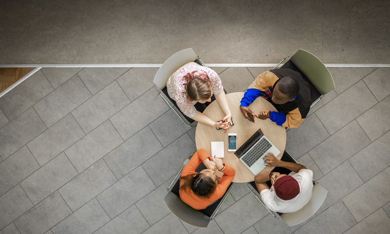 Aerial shot of four students working at round table