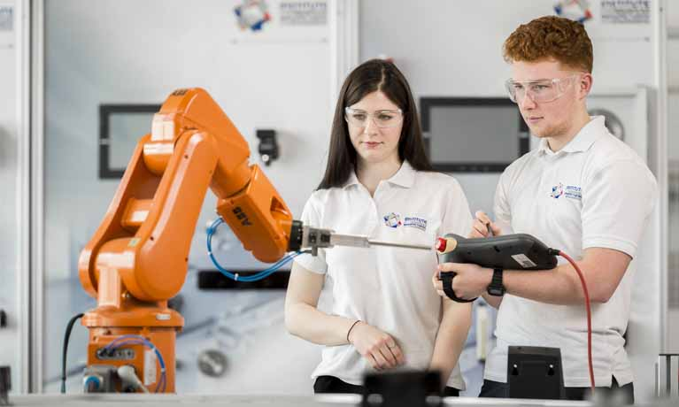 white female and male students working with cobot