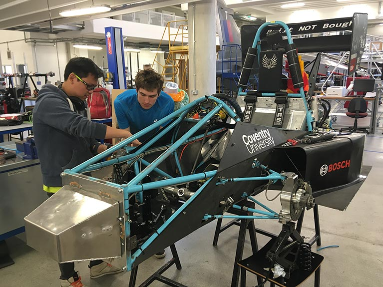 Motorsport engineering students Daniel Loh and Rob Sharp working on Phoenix Racing's car in the university's Engineering and Computing Building.