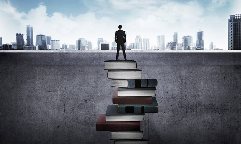 man standing on stack of books