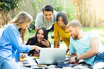 students-smiling-looking-at-laptop-in-park