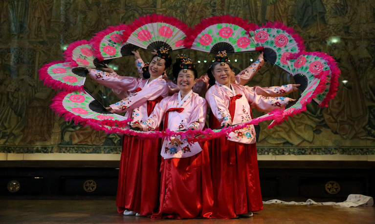 Korean female dancers in traditional dress forming a circle with fans.